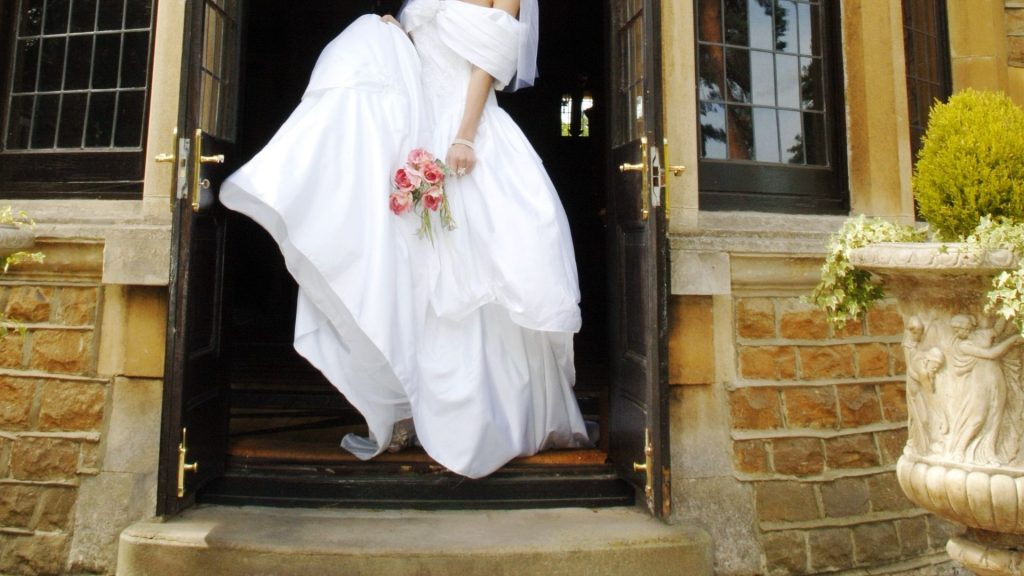 woman standing in wedding dress in doorway holding roses